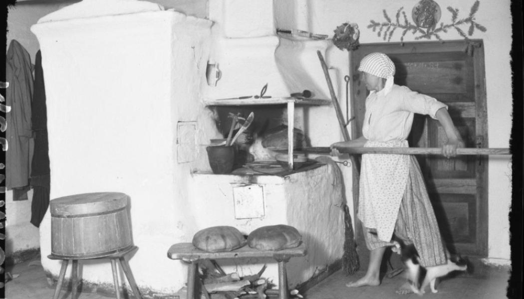 Czarno-białe zdjęcie przedstawiające kobietę w kuchni. Kobieta piecze chleb w glinianym piecu. W pomieszczeniu widoczne naczynia do przygotowywania chleba.