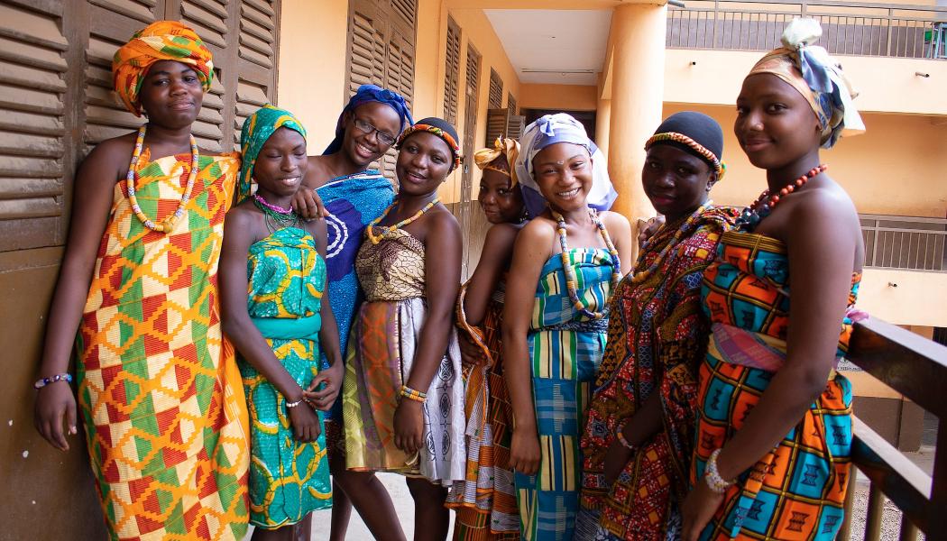 Zdjęcie przedstawiajace osiem, młodych, uśmiechniętych kobiet z Ghany w kolorowych stroajach tradycyjnych. Ubrane są w sukienki z wielobarwnych tkaninm turbany na głowach i koralikowa naszyjniki.