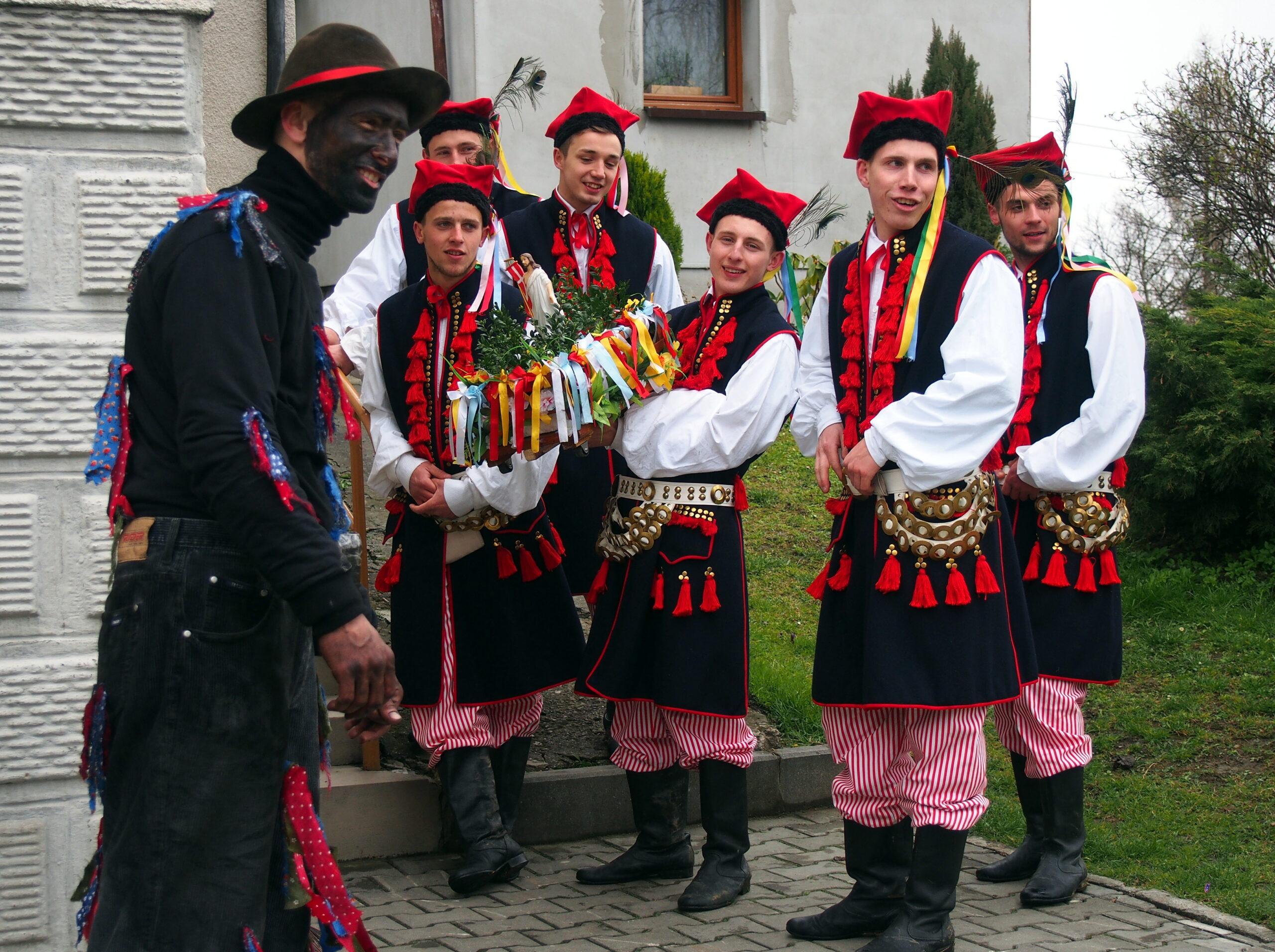Uczestnicy obrzędu Siuda Baba przd domem. Sześciu mężczyzn ubranych w regionaln stroje krakowskie, jeden z usmoloną twarzą jako Siuda Baba.
