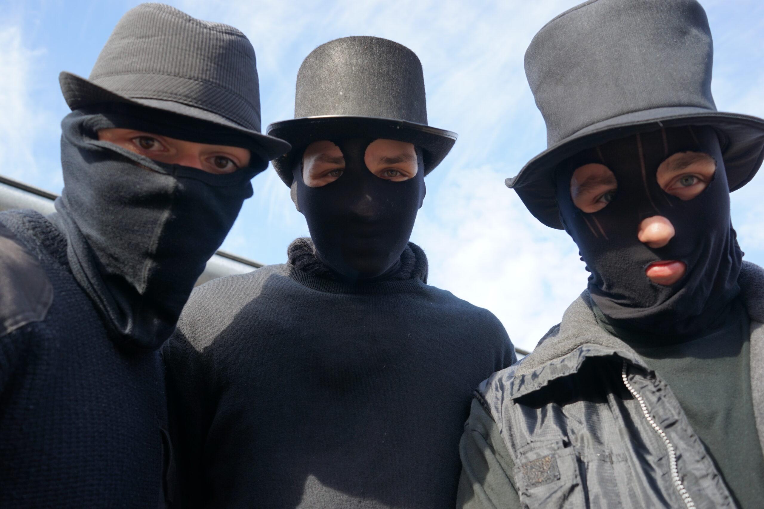 Na zdjęciu widać trzech ubranych na czarno uczestników Siwków. Mają na głowach czarne komuniarki i kapelusze.