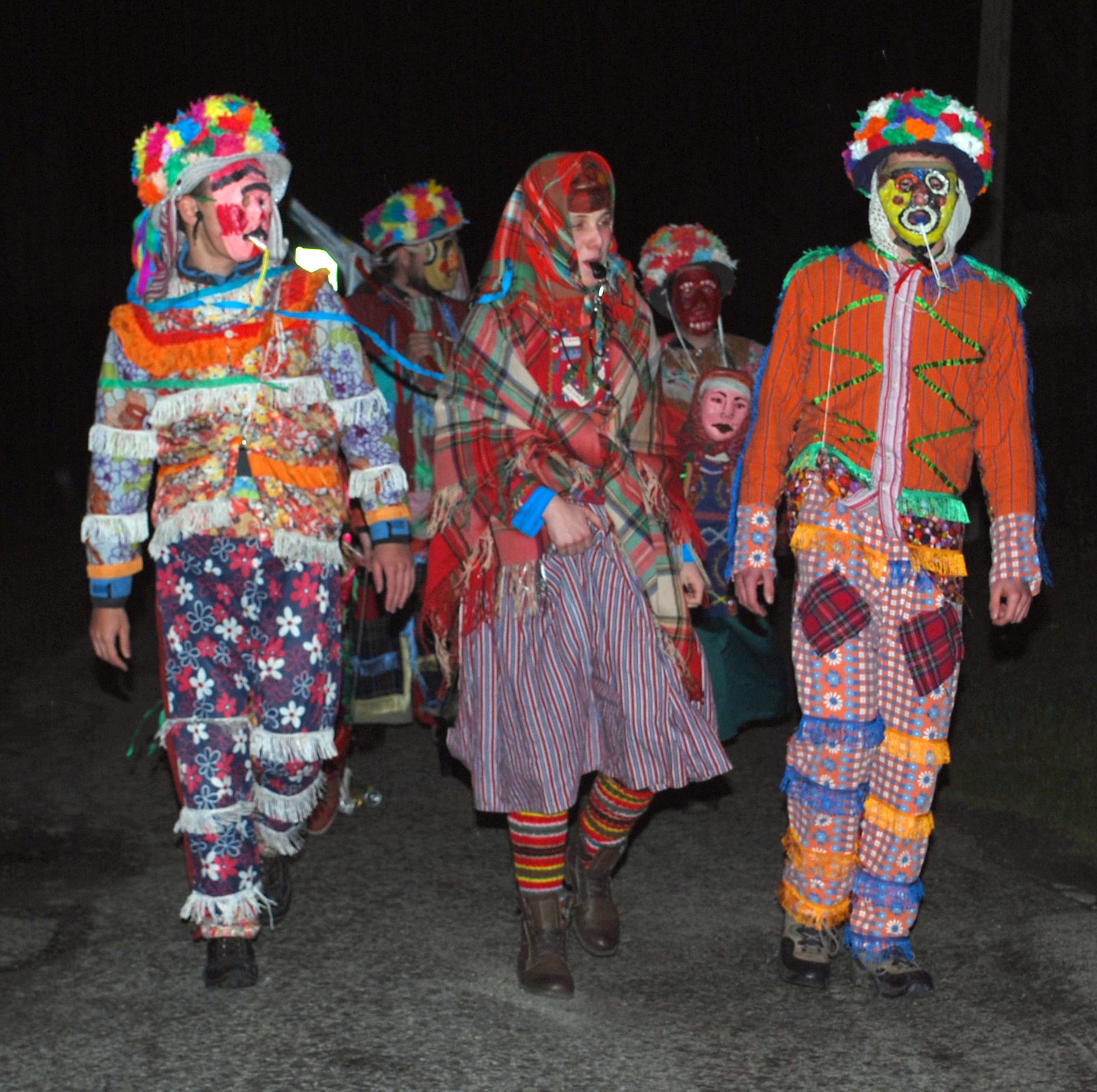 Na zdjęciu uczestnicy obrzędu Śmergust w pochodzie na ulicy. Ubrani w kolorowe kostiumy: ozdobne kapelusze, maski na w twarzach, kolorowe stroje.