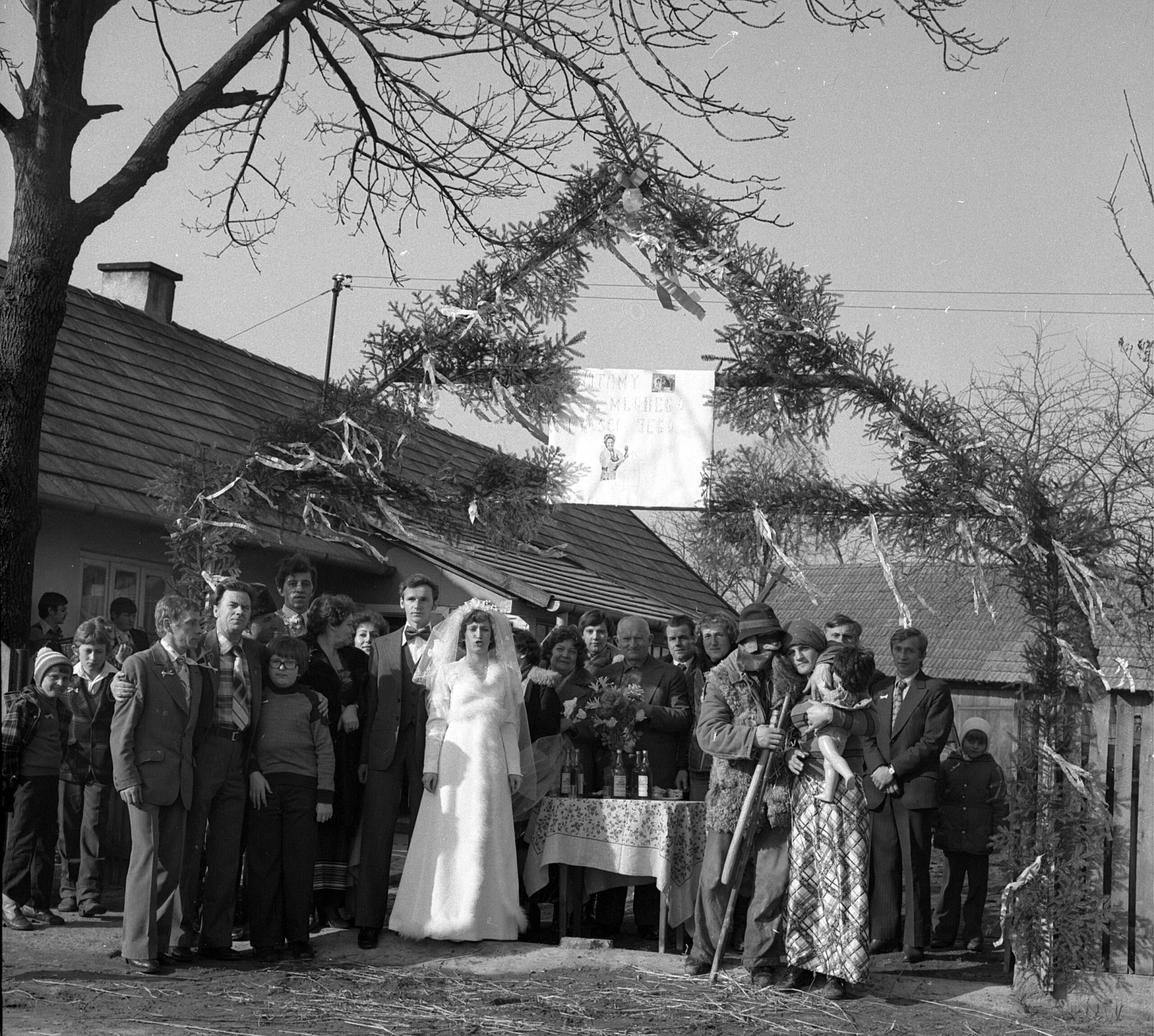 """Zdjęcie czarno-białe, Paraa młoda wraz z goścmi stoją przed stołem i wejściem do domu. Trwa """"wykupienie"""" pary młodej - bedą mogli przejść przez bramę po obrawaniu gości, którzy torują wejście w przebraniach, butelkami z alkoholem."""
