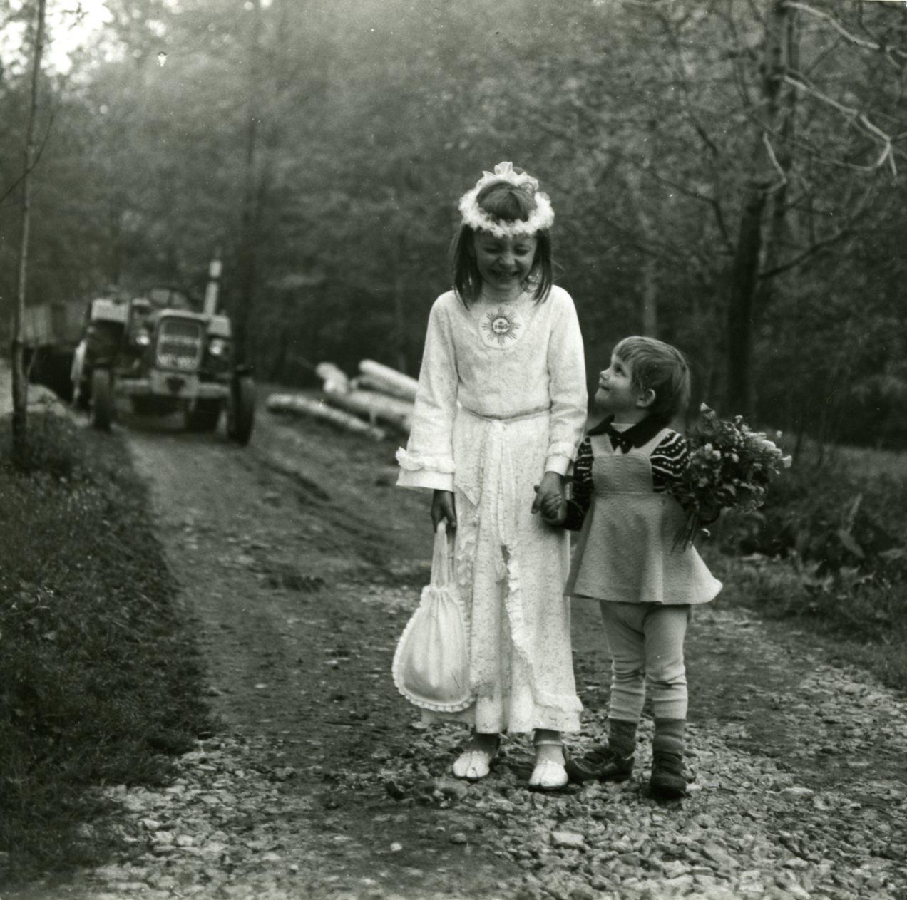 Dziewczynka w stroju komunijnym i wiankiem na głowie w towarzystwie młodszej siotry. Zdjęcie czarno-białe wykonane na leśniej ścieżce, w tyle widać traktor.