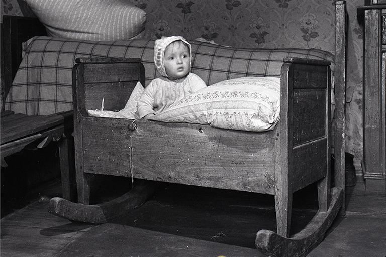 Dziecko w kołysce. Zdjęcie czarno białe. W tle kołyski - łóżko i ściana.