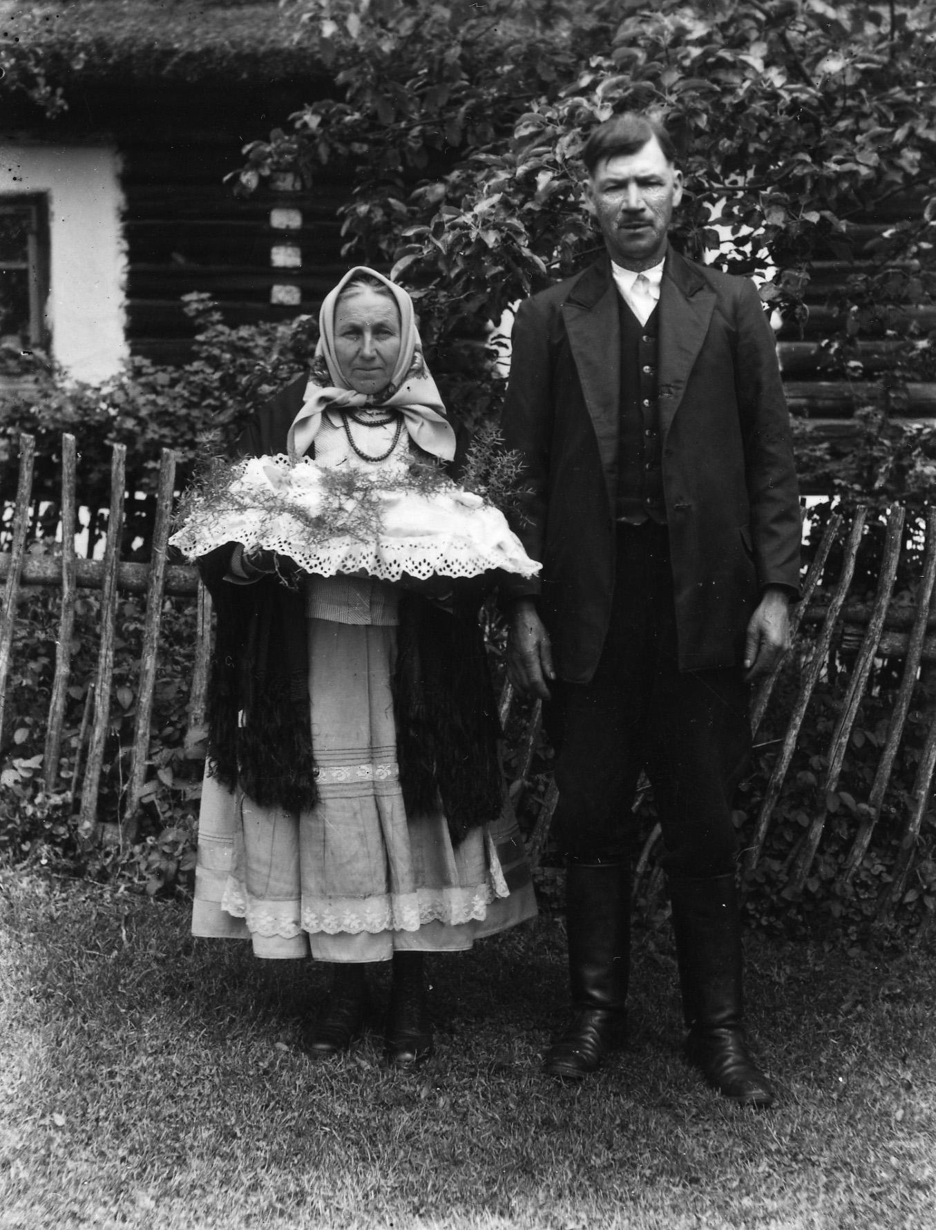 Zdjęcia czarno-białe. Kobieta i mężczyna odwiętnie ubrani stoją przed domem. Kobieta trzyma podszukę z dzieckie a niej leżą rośliny. Udją się na chrzest dziecka.