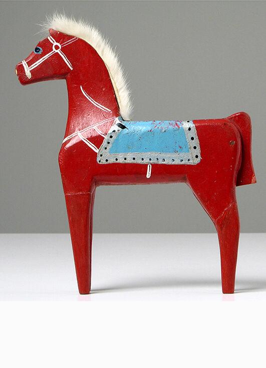 Czerwnony drewniany konik zabawka. Z białą grzywą i błękitnym sidłem namalowanym na grzbiecie.