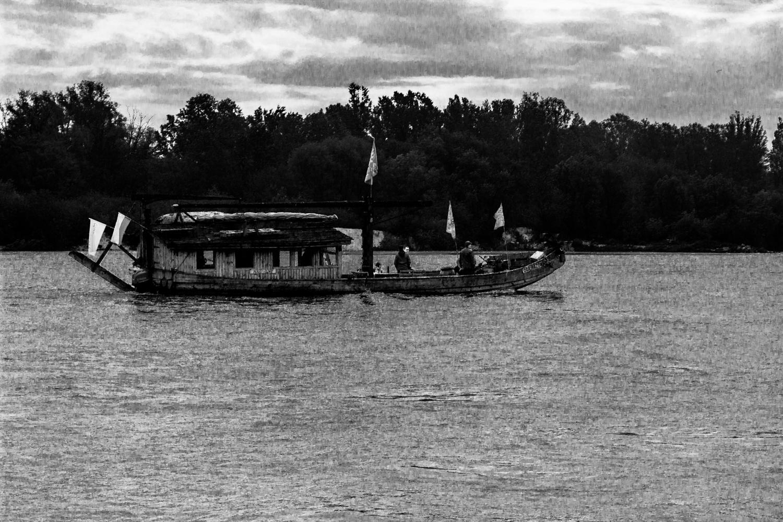 Zdjęcia czarno-białe przedstawiające pływajacą na Wiśle Szkutę Mazowsze - drewniany beznapędowy statek służący do transportu śródlądowego.