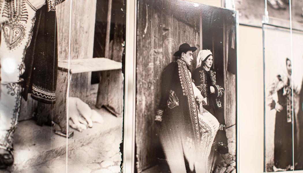 """Zdjęcia z wystawy """"fotogawęda"""". Czarno-białe fotografie umieszczone na szklanych taflach, które można oglądać z obu stron na wystawie. Kadr skupia się na fotografii przedstawiającej Mieczysława Cholewę i jego żonę w strojach Lachów Sądeckich."""