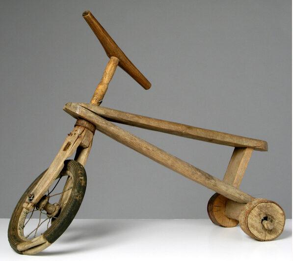 Rowerek – zabawka, z trzema kołami, wykonany z drewna.
