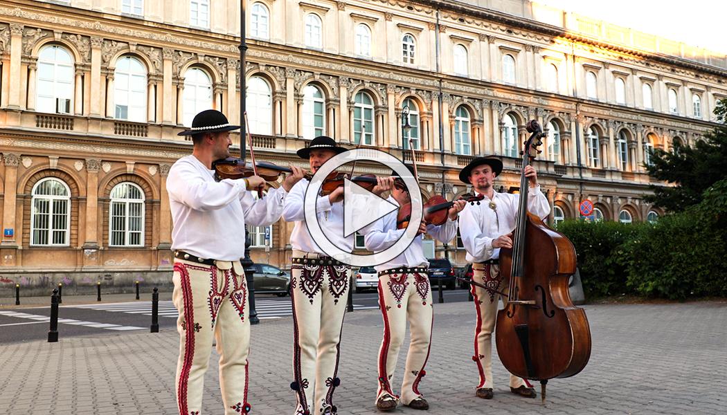 Góralski zespół Ciupaga gra na tradycyjnych instrumentach przed Państwowym Muzeum Etnograficznym na placu Małachowskiego