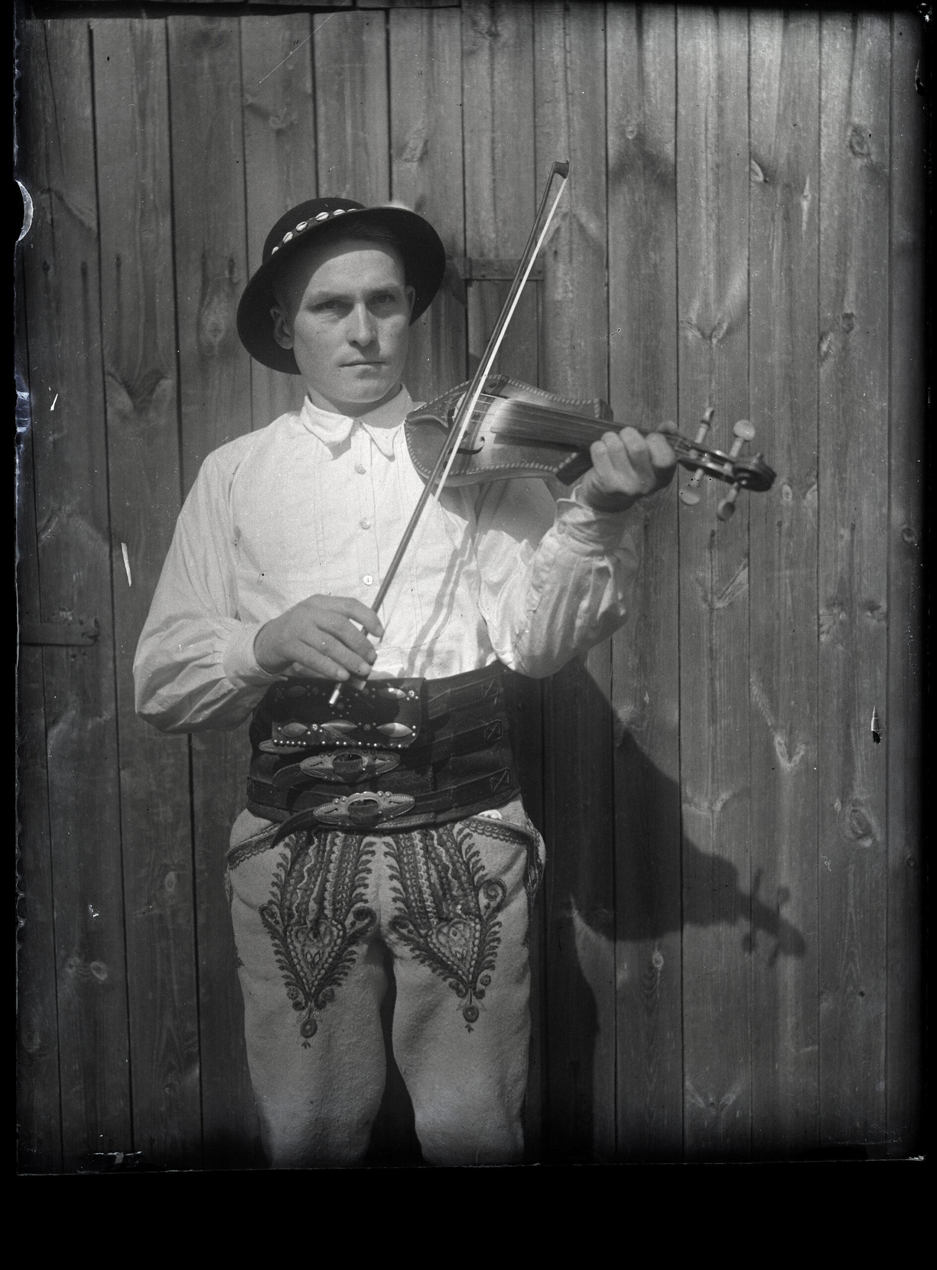 Franciszek Kurzeja w stroju łąckim grający na złóbcokach Józefa Zboźnia na tle drewnianej ściany. Negatyw szklany czarno-biały.