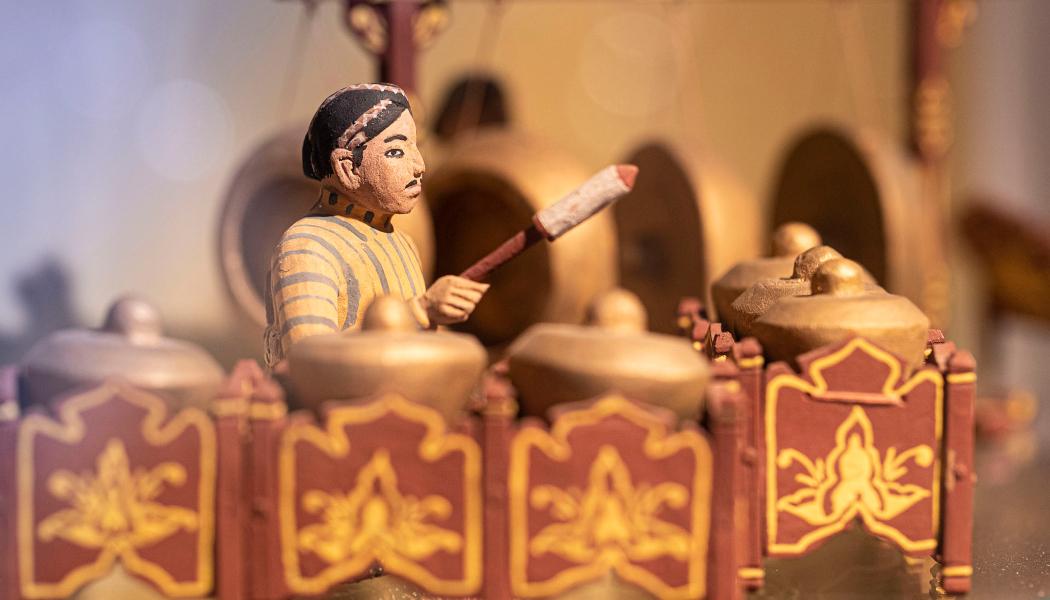 Rzeźba przedstawiająca secenkę rodzajową - mężczyzna grający na indyjskich instrumentach. Zdjęcie w czerwonej i żółtej kolorystyce.