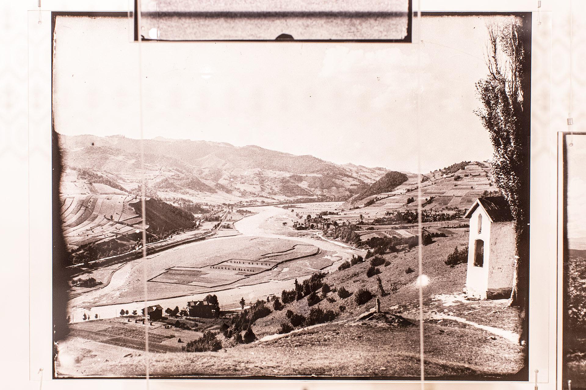 Zdjęcie umieszczone jako nakljenka na szklanej tafli. Prezentuje pejzaż okoli Nowego Sącza. Góry, widoczna dolinka, drzeaw i mała kapliczka z prawej strony w kadrze.