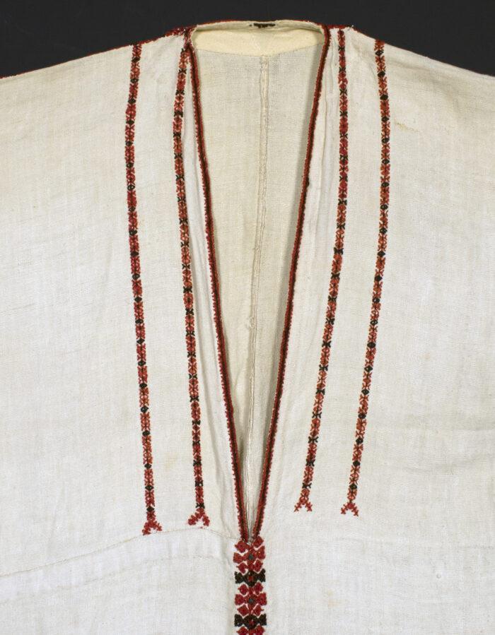 Zdjęcie przedstawia fragment lnianej, białej koszuli z drobnymi, czerwonymi naszyciami.