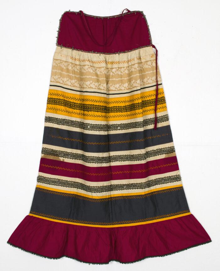 Fotografia prezentuje długą spódnicę - część stroju Mordowianki. Spódnica posiada pojedynczą falbanę u dołu. Materiał jest pasiasty: widać pasy koloru czerwonego, żółtego i czarnego. Dostrzegalne są drobne wzory na pasach.