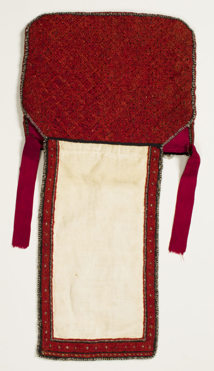 Zdjęcie prezentuje intensywnie czerwony czepiec nakładany na głowę. Tył czepca jest wydłużony tak, by opadał na barki osoby noszącej akcesorium odzieżowe.