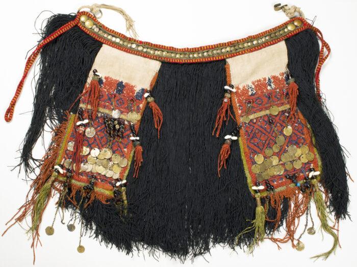 Zdjęcie prezentuje zapasek kobiecy w ciemnych barwach z jasnymi doszyciami. Cała ta część garderoby Mordowianek pokryta jest frędzlami.