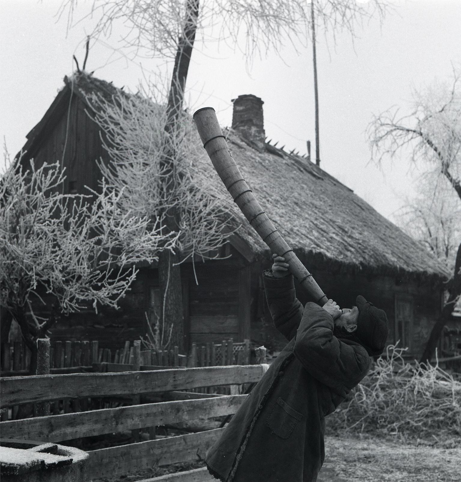 Czarno-białe zdjęcie. Mężczyna grający na ligawie na tle wiejskiej zabudowy.