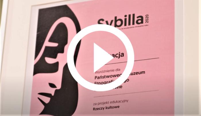 Zdjęcie prezentujące wyróżnienie w konkursie Sybilla dla PME. Na środku fotografii znajduje sie ikonka odtwarzania. Zdjęcie jest łączem do krótkiego filmu prezentującego w skrócie projekt Rzeczy Kultowe.